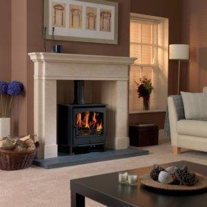 Astwood Wood burner lit in solid stone fireplace